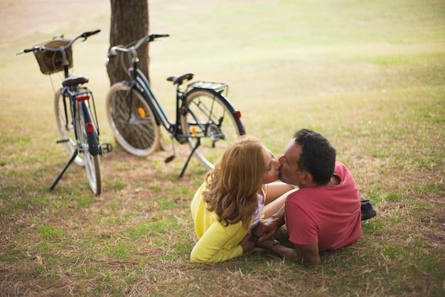 公園でキス幸せな成熟したカップルの肖像画。秋の屋外でデート自転車を持つ年配の男性と女性