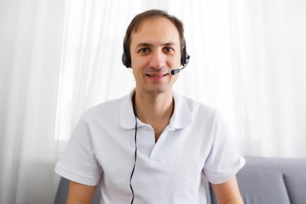 이어폰을 끼고 노트북에서 화상 통화를 하며 손짓을 하는 행복한 성숙한 남자의 초상화. 집에서 화상 통화를 하는 쾌활한 캐주얼 사업가입니다.