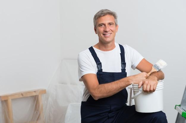 Портрет счастливой зрелой художницы со стремянкой и ведром с краской