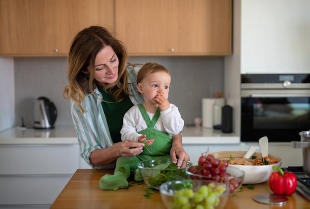 家庭料理の屋内で小さな赤ちゃん孫娘と幸せな成熟した女性の肖像画。