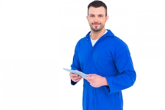 Portrait of happy mechanic pointing on digital tablet on white background