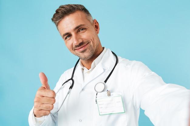 青い壁の上に孤立して立っている間、聴診器でselfie写真を撮る幸せな医師の肖像画