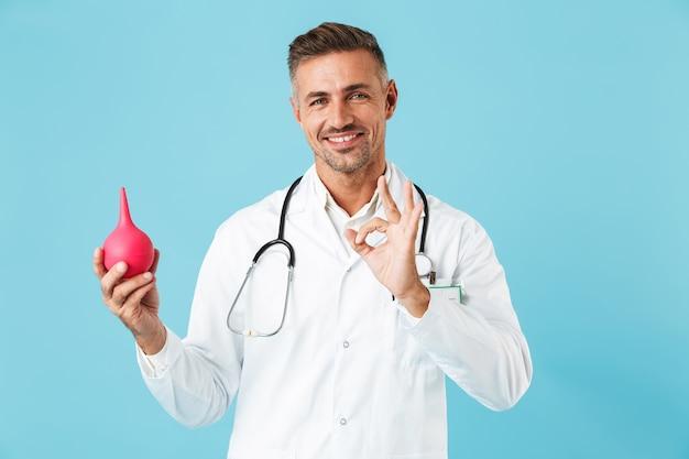 浣腸を保持し、青い壁の上に孤立して立っている白いコートを着て幸せな医療専門家の肖像画