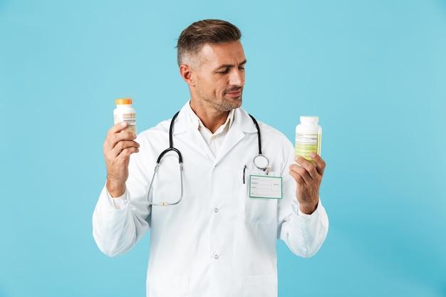 青い壁の上に孤立して立って、錠剤の瓶を保持している白いコートを着て幸せな医療専門家の肖像画