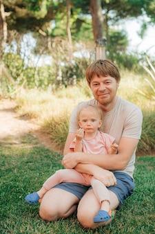 잔디에 앉아 아기 딸과 함께 행복 중반 성인 남자의 초상화