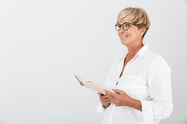 Портрет счастливой женщины средних лет в очках, держащей книгу и смотрящей в сторону, изолированной над белой стеной в студии
