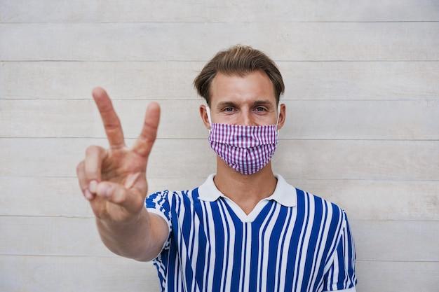 コロナウイルス拡散防止のための医療用保護マスクを着用しながら親指で笑って幸せな千年の男の肖像