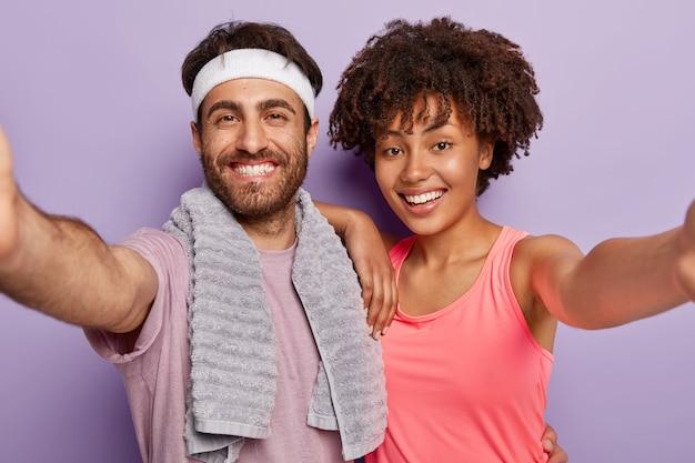 Портрет счастливой женщины и мужчины смешанной расы берут селфи-портрет, позитивно улыбаются, одетые в спортивную одежду, активно тренируются, изолированные на фиолетовой стене студии