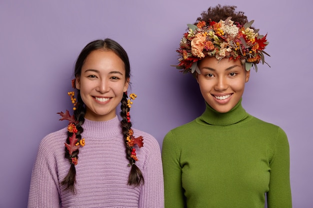 따뜻한 옷을 입은 행복한 혼혈 여성의 초상화, 단풍으로 장식 된 머리카락, 좋은 감정을 표현하고 서로 옆에 서 있습니다.