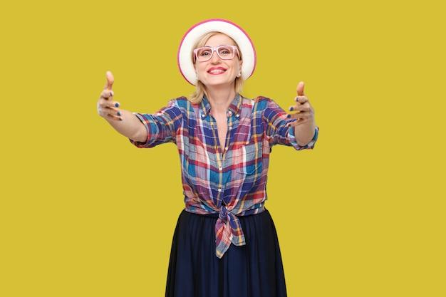 帽子と眼鏡が立って抱きしめ、歯を見せる笑顔で見ているカジュアルなスタイルの幸せでモダンなスタイリッシュな成熟した女性の肖像画。黄色の背景に分離された屋内スタジオショット。
