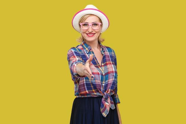 Портрет счастливой современной стильной зрелой женщины в повседневном стиле с шляпой и очками, стоящей с зубастой улыбкой, смотрящей и протягивающей руку приветствию. крытая студия выстрел, изолированные на желтом фоне.