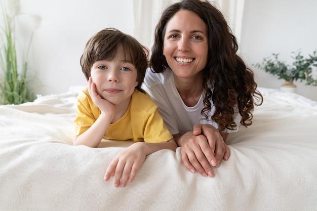 행복한 엄마와 아들이 함께 편안한 첫 휴일 아침에 침대에 누워 있는 초상화
