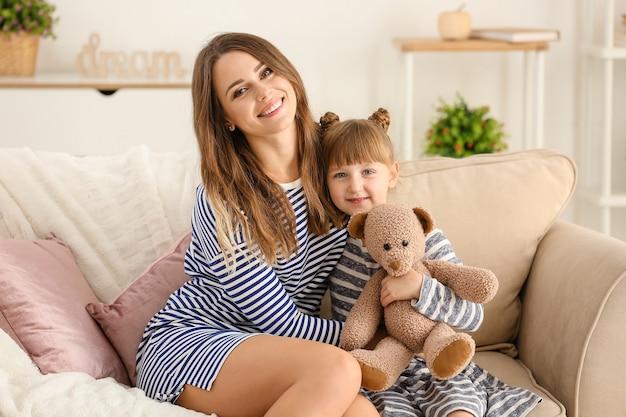 自宅のソファに座っている幸せな母と娘の肖像画