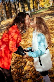 秋の色の木の葉で幸せな母と娘の肖像画