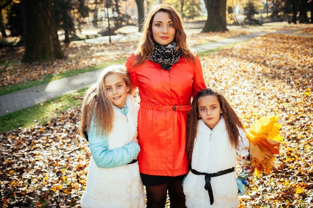 娘の手に木の葉と日没の秋の森で幸せな母と娘の肖像画