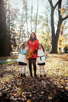 행복 한 어머니와 나무 석양 가을 숲에서 그녀의 딸의 초상화는 그녀의 손에 나뭇잎