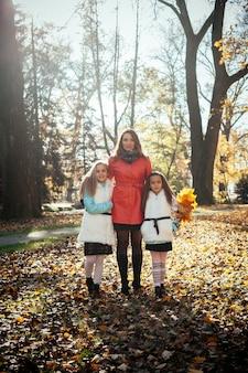 彼女の手に木の葉と日没の秋の森で幸せな母と娘の肖像画