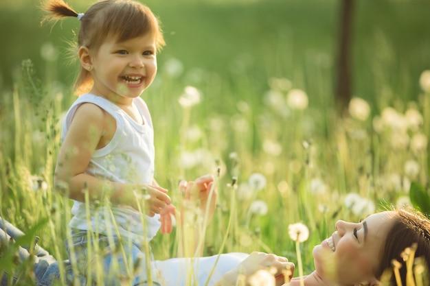 Портрет счастливой матери и ее маленького ребенка весной. жизнерадостная семья на поле одуванчика. мама и ее милая дочь outdoors.