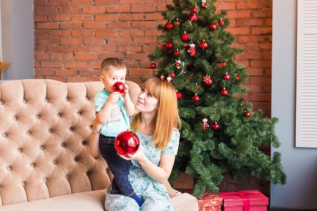 幸せな母親と笑う赤ちゃんの肖像画と国内のお祭りのインテリアに対して安物の宝石を保持