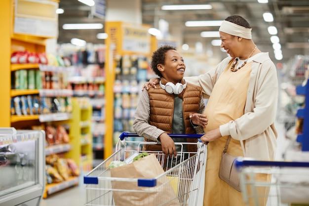 Портрет счастливой матери и сына, делающих покупки в супермаркете и толкающих продуктовую тележку, копировальное пространство