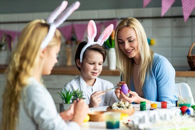 행복 한 어머니, 아들 및 딸의 초상화는 부활절을 준비하는 동안 계란을 그림입니다. 어머니는 아들을 돕습니다.