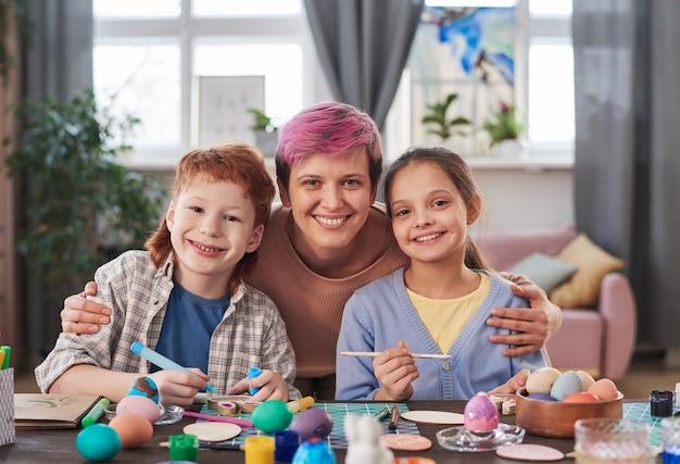 부활절 달걀을 장식하고 그림을 그리는 동안 카메라를 보며 웃고 있는 두 자녀와 함께 있는 행복한 어머니의 초상화