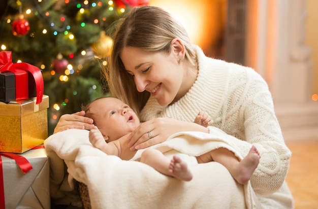 크리스마스 트리 아래 갓 태어난 아기와 함께 행복 한 어머니의 초상화