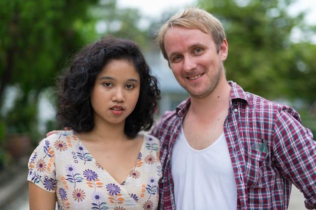 屋外の通りで一緒に幸せな多民族のカップルの肖像画