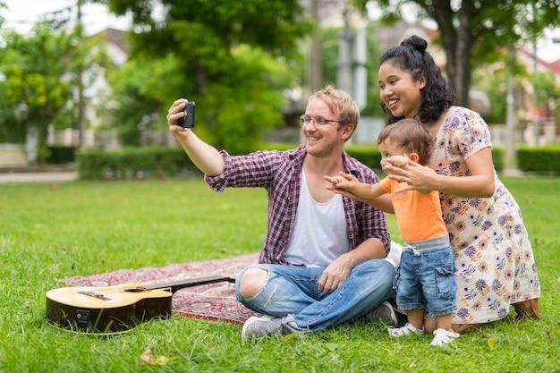 1人の子供が屋外で一緒に結合している幸せな多民族家族の肖像画