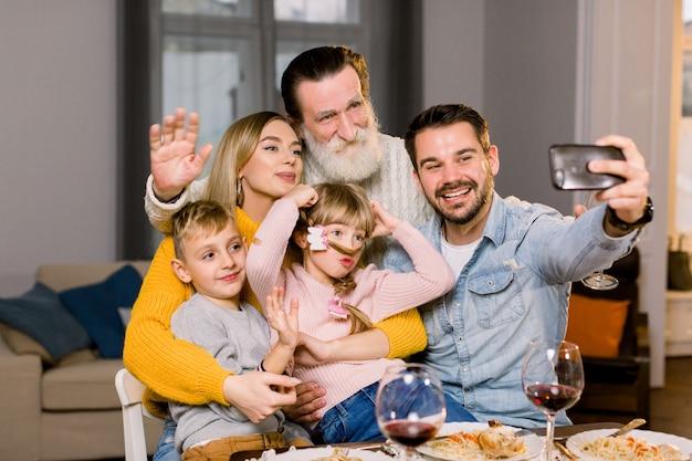 夕食のテーブルに座ってselfie写真を撮る幸せな多世代家族の肖像画