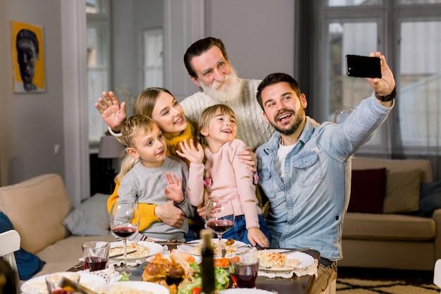 休日を祝っている間夕食のテーブルに座ってselfie写真を撮る幸せな多世代家族の肖像画