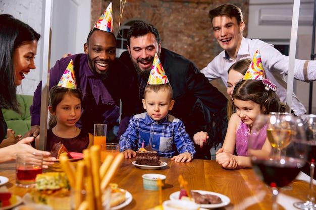 집에서 생일을 축하하는 행복 다민족 가족의 초상화. 큰 가족이 케이크를 먹고 와인을 마시면서 인사하고 아이들을 즐겁게합니다. 축하, 가족, 파티, 홈 개념.