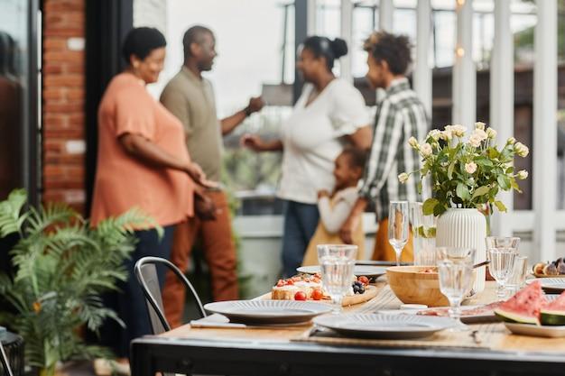 テラスのコピースペースで屋外のディナーパーティー中におしゃべり幸せな多世代家族の肖像画