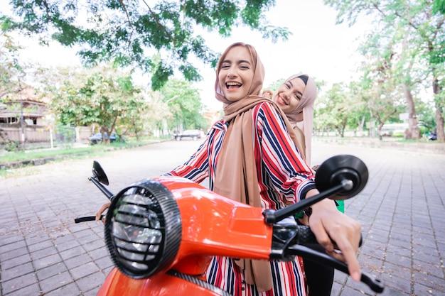 스쿠터를 타고 행복 이슬람 소녀의 초상화는 친구와 함께 여름 휴가를 즐길 수