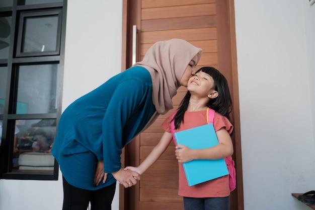 행복 한 이슬람 어머니의 초상화 학교 하루 전에 집에서 아침에 그녀의 아이 뺨에 키스