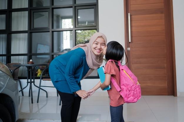 Портрет счастливой мусульманской матери целует своего ребенка в щеку утром дома перед учебным днем