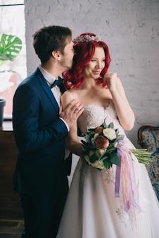 로프트 스타일의 방에서 웃고 껴안는 행복한 신혼 부부의 초상화