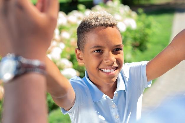 Портрет счастливого приятного радостного мальчика, улыбающегося своему отцу