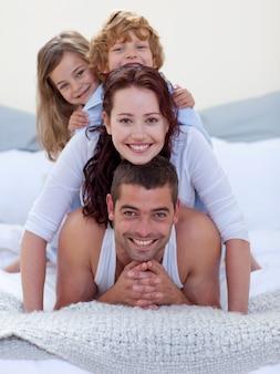 행복한 부모와 자녀가 침대에서 재미의 초상화 프리미엄 사진
