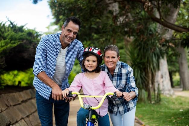 딸이 공원에서 자전거를 타도록 돕는 행복한 부모의 초상