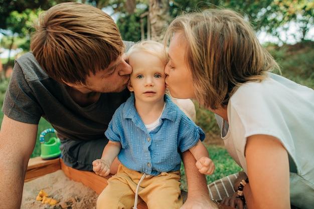 모래 구덩이에서 아이를 키스 하는 행복 한 부모의 초상화
