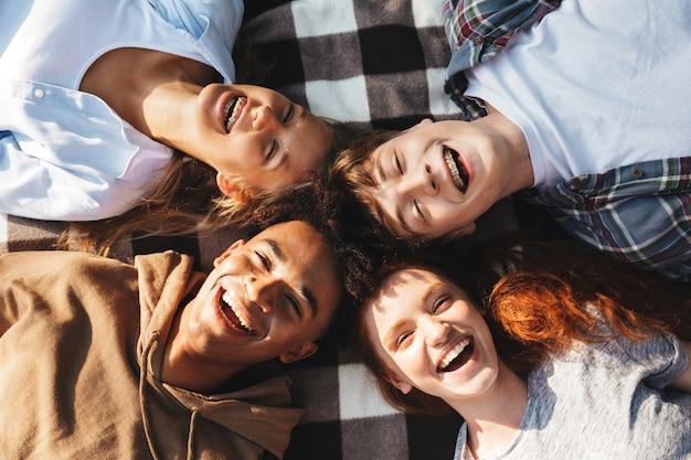 행복한 사람들의 초상화 남성과 여성은 웃고, 야외 원에서 담요에 누워