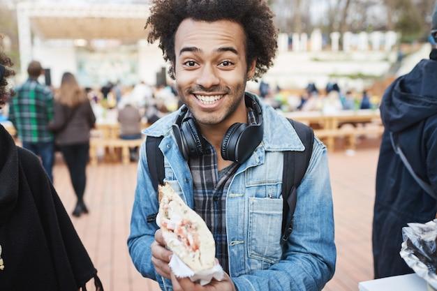 サンドイッチを押しながらカメラに向かって笑みを浮かべ、味わうことに興奮し、地元の公園のフードフェスティバルを歩いて喜んで幸せなアフリカ系アメリカ人のブロガーの肖像画。