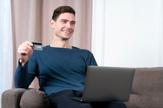 행복 한 긍정적 인 사람 쾌활 한 젊은이의 초상화는 자신의 노트북에서 인터넷 온라인 쇼핑을 즐기고있다