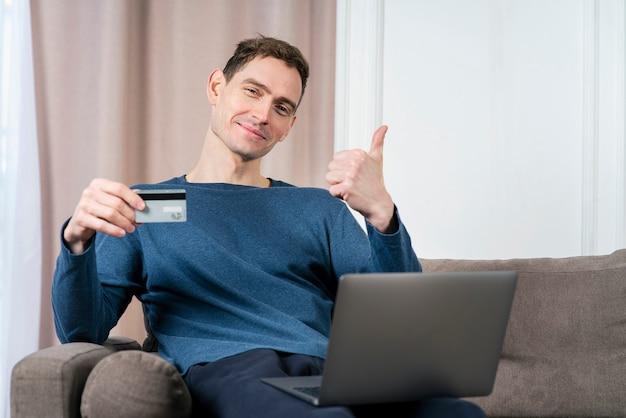 신용 은행 카드와 노트북을 손에 들고 행복 긍정적 인 사람 젊은 잘 생긴 남자의 초상화