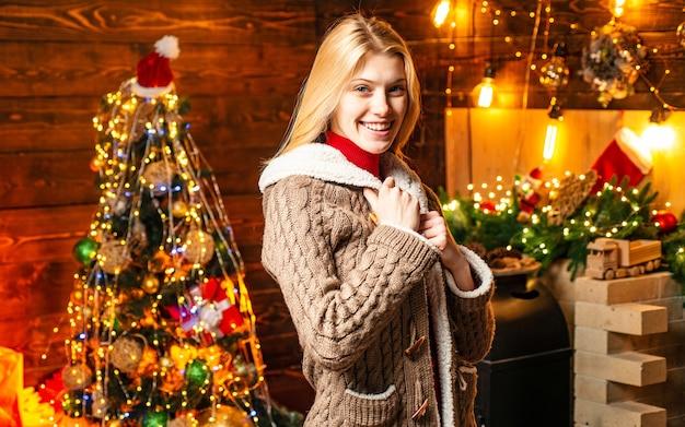 장식 된 방에 나무 배경에 서 행복 긍정적 인 여자의 초상화. 가족 휴가