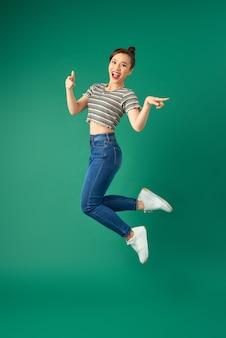 緑の上にジャンプして手を振って幸せなポジティブな若いアジアの女性の肖像画。