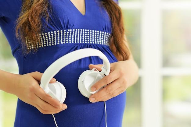ヘッドフォンで幸せな妊婦の肖像画
