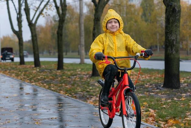 Портрет счастливого дошкольника в желтом плаще. мальчик едет на велосипеде в осеннем парке под дождем вокруг города.