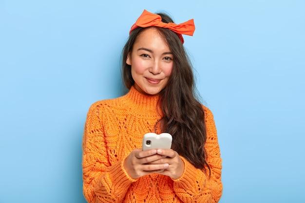 긴 머리를 가진 행복 예쁜 아시아 여자의 초상화, 머리띠와 주황색 스웨터를 입고 채팅을 위해 휴대 전화를 보유하고 새로운 응용 프로그램을 다운로드합니다.